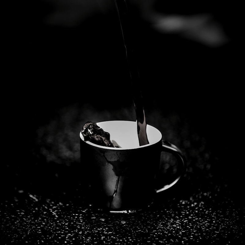 black and white photo of coffee being poured into a mug