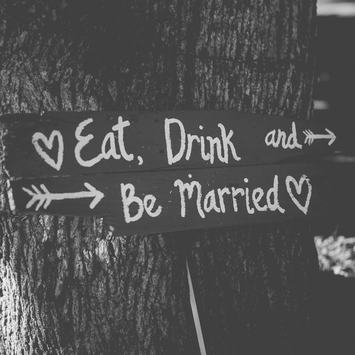 eat drink and be married sign on a tree at a wedding