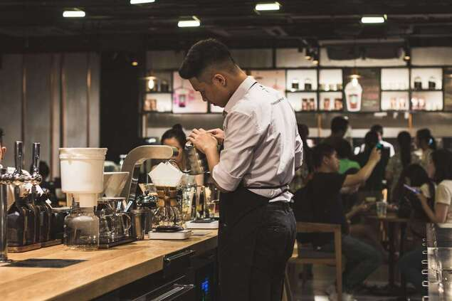 men's brown dress shirt and black pants making cofee inside a cafe